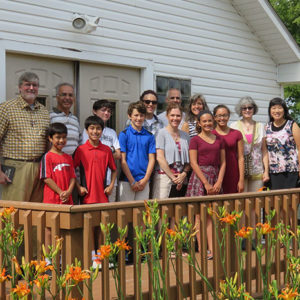 Members of the Global Mission Committee stand outside a chapel in Minnesota during the Pejuhatizizi Family Learning Camp.