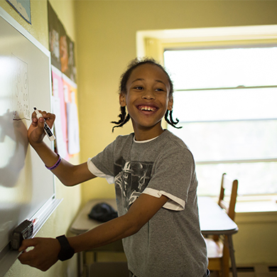 A Brown Memorial Tutoring Program students smiles as he writes on a dry erase board in a classroom at Brown Memorial.
